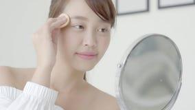Portrait beautiful young asian woman applying powder puff at cheek makeup of cosmetic looking mirror