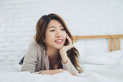 Beautiful young Asian woman on bed at home in the morning. Cheerful Asian woman wearing a comfortable sweater and smiling. Portrait beautiful young Asian woman royalty free stock photo