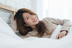 Portrait beautiful young Asian woman on bed at home in the morning. Cheerful Asian woman wearing a comfortable sweater and smiling on her bed. Relaxing room royalty free stock photography
