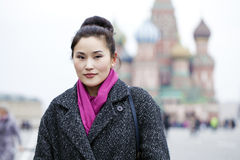 Portrait of a beautiful young asian woman in a gray coat on a re Stock Photo