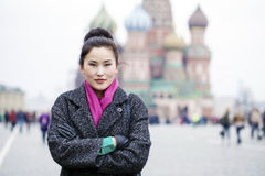 Portrait of a beautiful young asian woman in a gray coat on a re Royalty Free Stock Image