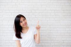 Portrait of beautiful young asian woman happiness standing finger pointing something on gray cement texture. Grunge wall brick background, businesswoman is a Royalty Free Stock Image
