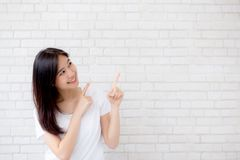 Portrait of beautiful young asian woman happiness standing finger pointing something on gray cement texture background royalty free stock photo
