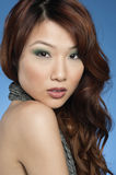 Portrait of a beautiful young Asian woman over colored background Stock Photography