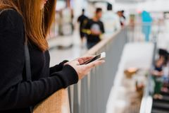 Portrait of beautiful young asian woman in shopping mall, smiling using smart phone to network indoors. Stock Image