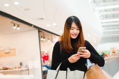 Portrait of beautiful young asian woman in shopping mall, smiling using smart phone to network indoors. Tourist woman using technology, travel lifestyle Royalty Free Stock Images