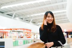 Portrait of beautiful young asian woman in shopping mall, smiling using smart phone to network indoors. Tourist woman using technology, travel lifestyle Stock Photography