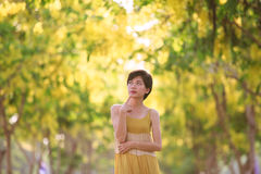 Portrait of beautiful young asian woman thinking against yellow Stock Photo