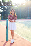 Portrait of beautiful young asian woman waearing white clothes s. Kirt in tennis course with happy face Stock Image