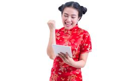 Portrait of Beautiful Young asian woman wear chinese dress traditional cheongsam or qipao using modern digital tablet Royalty Free Stock Images