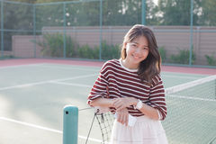 Portrait of beautiful young asian woman wearing white clothes sk. Irt in tennis course with happy face Stock Image