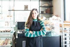 Confident Saleswoman Wearing Apron In Bakery. Portrait of beautiful young bakery owner standing arms crossed in shop royalty free stock photography