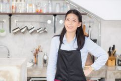 Portrait of beautiful young barista, asian woman is a employee. Standing in counter coffee shop, service concept Royalty Free Stock Photo