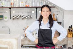 Portrait of beautiful young barista, asian woman is a employee standing in counter coffee shop. Service concept Royalty Free Stock Photography