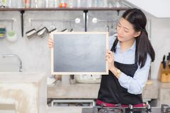 Portrait of beautiful young barista, asian woman is a employee standing holding chalkboard. In counter coffee shop, service concept Stock Photo