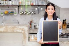 Portrait of beautiful young barista, asian woman is a employee standing holding chalkboard. In counter coffee shop, service concept Stock Photos