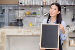 Portrait of beautiful young barista, asian woman is a employee standing holding chalkboard. Portrait of beautiful young barista, asian woman is a employee Royalty Free Stock Photos