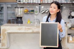 Portrait of beautiful young barista, asian woman is a employee standing holding chalkboard. Portrait of beautiful young barista, asian woman is a employee Royalty Free Stock Image