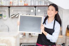 Portrait of beautiful young barista, asian woman is a employee standing holding chalkboard. Portrait of beautiful young barista, asian woman is a employee Stock Images