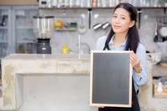 Portrait of beautiful young barista, asian woman is a employee standing holding chalkboard. Portrait of beautiful young barista, asian woman is a employee Stock Image