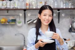 Portrait of beautiful young barista drinking a cup of coffee. Asian woman is a employee standing in counter coffee shop, service concept Stock Images