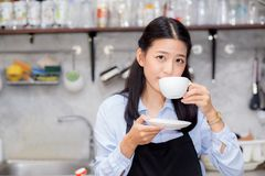 Portrait of beautiful young barista drinking a cup of coffee. Asian woman is a employee standing in counter coffee shop, service concept Royalty Free Stock Photos