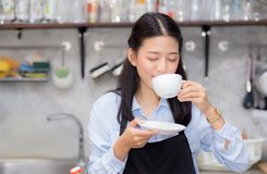 Portrait of beautiful young barista drinking a cup of coffee. Asian woman is a employee standing in counter coffee shop, service concept Stock Image