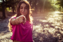 Portrait of beautiful young blinking woman against the sun background. Portrait of beautiful young blinking woman in shorts against the sun background standing stock photo