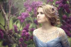 Portrait of a beautiful young blond woman in lilac bushes, admiring flowers.