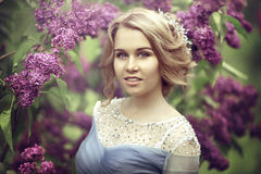 Portrait of a beautiful young blond woman in lilac bushes, admiring flowers. stock images