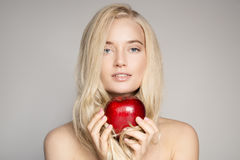 Portrait Of A Beautiful Young Blond Woman With Red Apple. Stock Photography