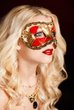 Portrait of a beautiful young blond woman with theatrical mask on his face on a dark background Stock Photo