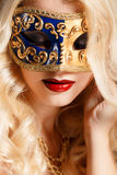 Portrait of a beautiful young blond woman with theatrical mask on his face on a dark background Royalty Free Stock Photos