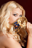 Portrait of a beautiful young blond woman with theatrical mask on his face on a dark background Royalty Free Stock Images