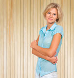 Portrait of beautiful young blonde on background of wooden wall Stock Photo