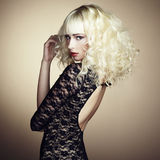 Portrait of beautiful young blonde girl in black dress. Fashion photo stock image