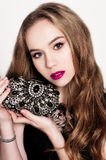 Portrait of beautiful young blonde girl in black dress holfing her handbag. Fashion photo, close up Stock Photography