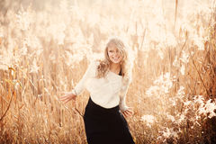 Portrait of a beautiful young blonde girl in a field in white pullover, laughing Stock Image