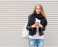 Portrait of a beautiful young blonde girl with long hair posing on a street with coffee and a backpack. Look at the camera. Outdoo Royalty Free Stock Photography