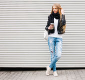 Portrait of a beautiful young blonde girl with long hair posing on a street with coffee and a backpack. Outdoor, warm color. Royalty Free Stock Image