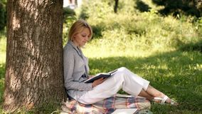 Portrait of beautiful young blonde girl reading a book in the park. Portrait of happy student relaxed outdoors reading stock footage