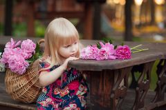 Portrait of a beautiful young blonde girl sitting next to a basket of flowers stock photos