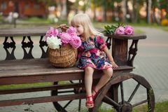 Portrait of a beautiful young blonde girl sitting next to a basket of flowers stock photo