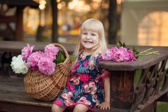 Portrait of a beautiful young blonde girl sitting next to a basket of flowers royalty free stock image