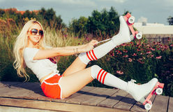 Portrait of a beautiful young blonde girl tighten the laces sitting on a bench in a vintage roller skates, wearing shorts, golfs a Stock Photography