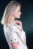 Portrait of a beautiful young blonde. Young girl in a white jacket and black skirt on a dark background Stock Image