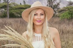 Portrait. Beautiful young blonde in a hat posing on the prairie in the field. royalty free stock image