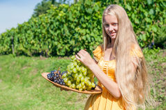 Portrait of a beautiful young blonde holding bowl of grapes Royalty Free Stock Photos