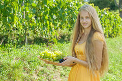 Portrait of a beautiful young blonde holding bowl of grapes Stock Photography