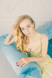 Portrait of a beautiful young blonde in a long gold dress on the couch . Studio. High-fashion. Emotions Stock Images